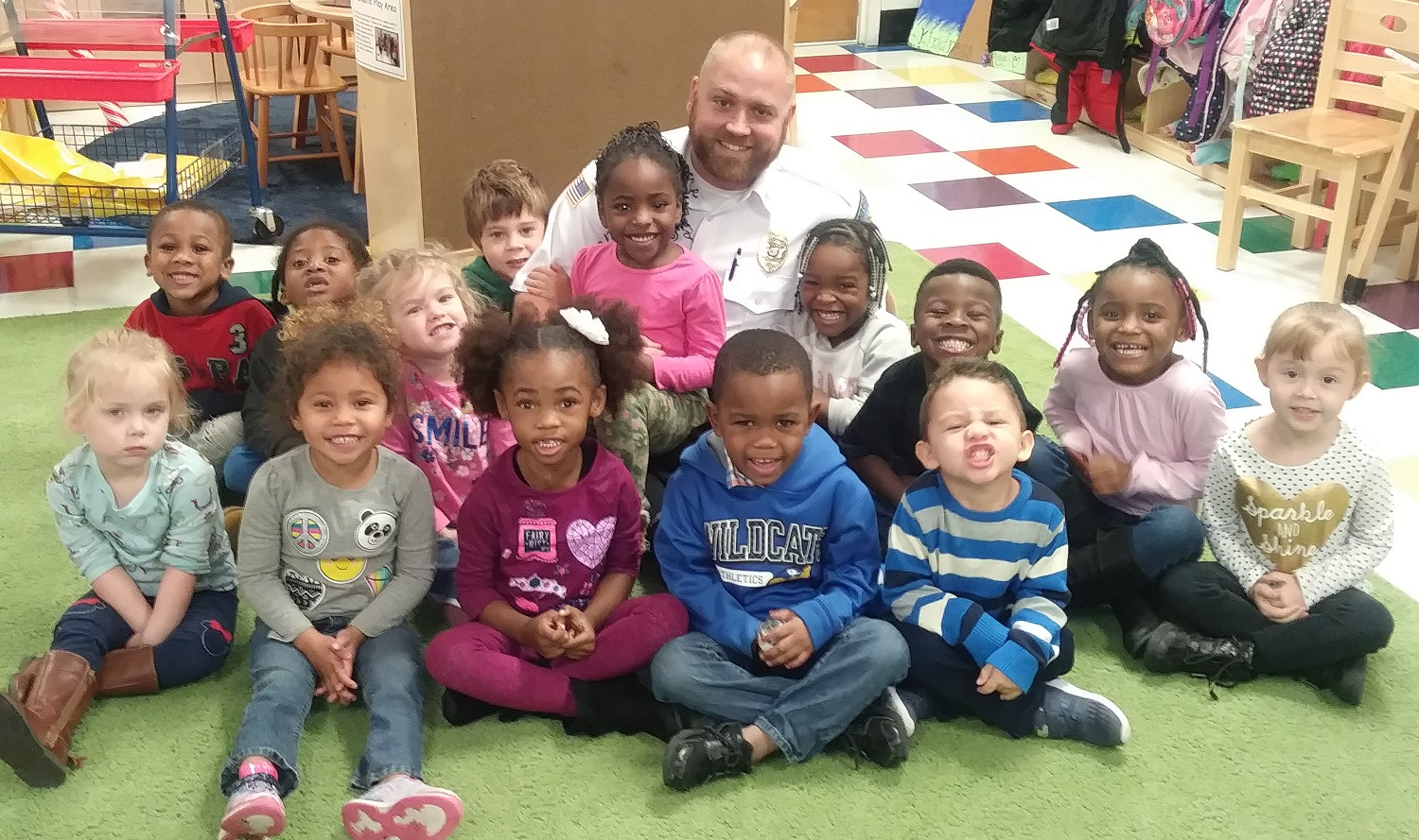 Corrections officer sitting on the floor with a dozen preschoolers