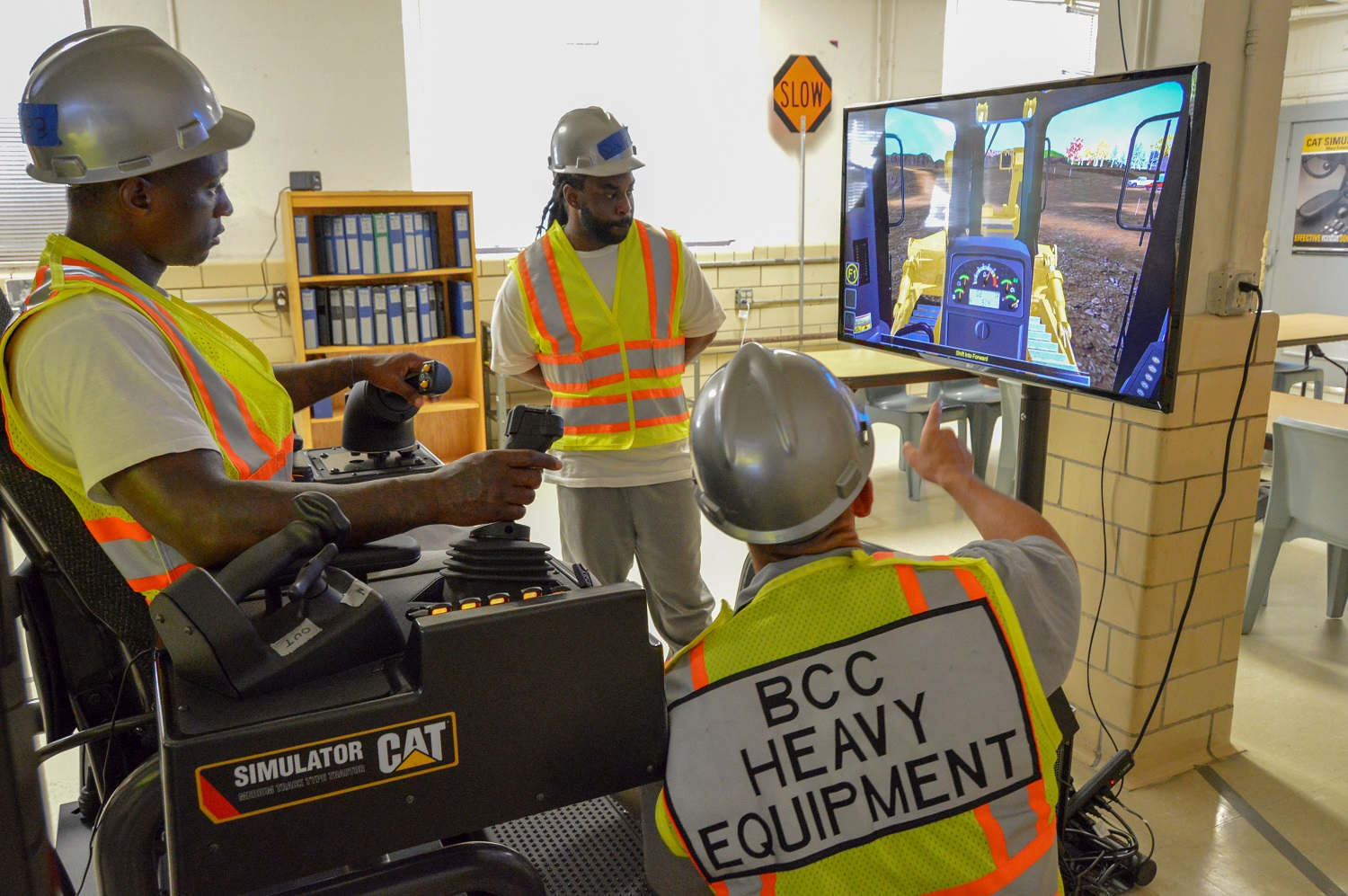 Man in hard hat operating a simulator, with two other men watching.