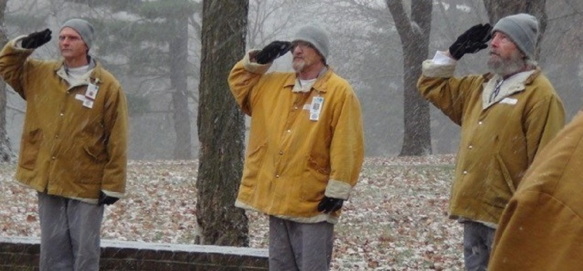 Three men in prison uniforms standing in falling snow and saluting a flag.