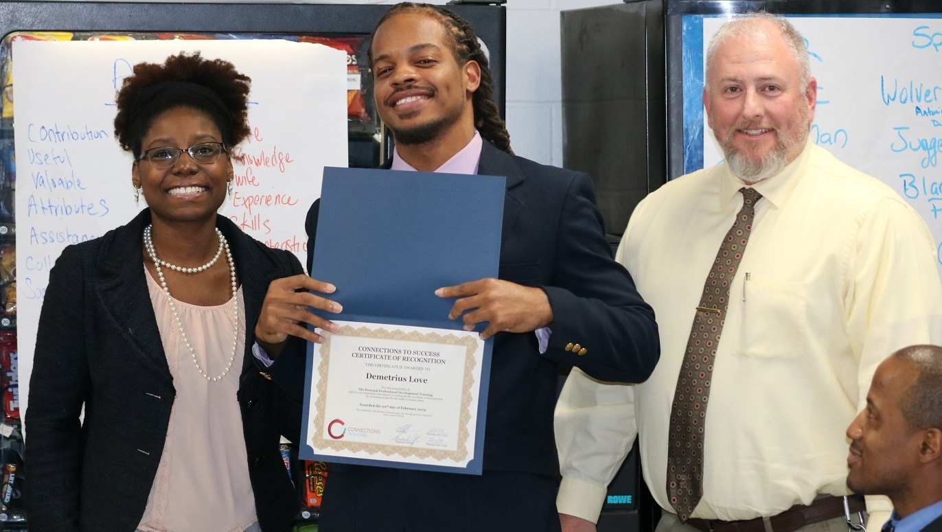 An offender holding a diploma poses with two staff members.