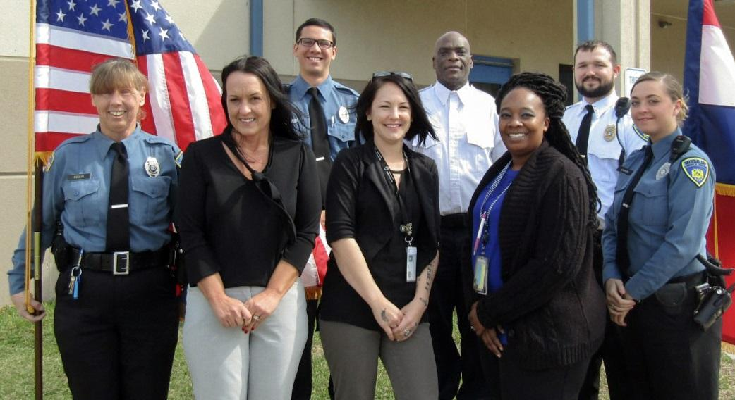 Group of corrections officers in uniform standing by a U.S. flag.