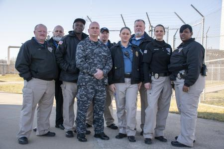 Nine officers in uniform in front of a fence.