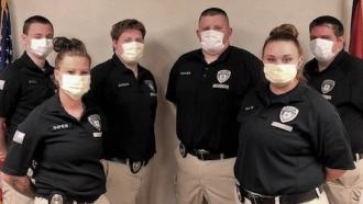 Six officers in uniform pose wearing fabric face covers.